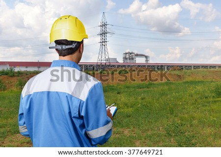 builder in yellow helmet with documents in hand, looking at the outline of the plant