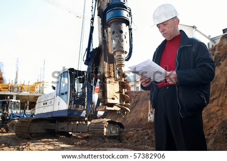 builder inspector worker at construction site with documentation