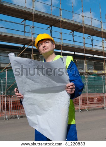 Builder inspects plans and buildings on construction site. - stock photo