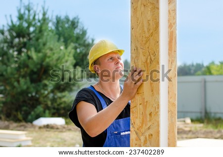 Builder installing wall insulation holding upright a wooden insulated polystyrene beam in a vertical position on a building site - stock photo