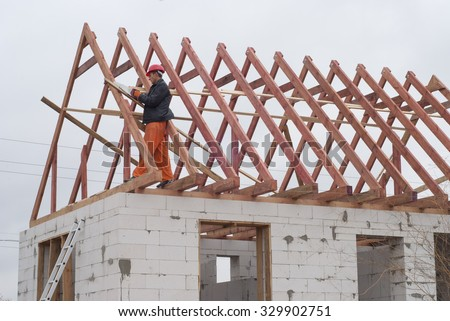 builder is installing roof system on the house of aerated concrete - stock photo
