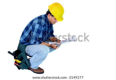 Builder kneeling reading a Blueprint - stock photo