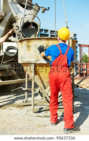 builder laborer man working with front of concrete cement mixer at construction site - stock photo