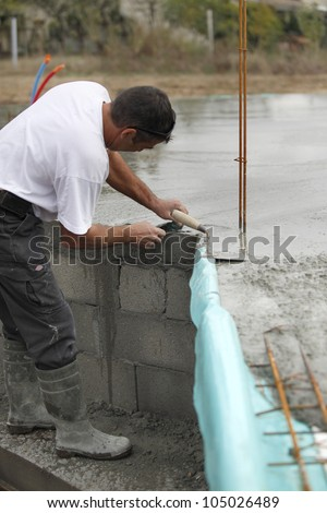 Builder laying foundations - stock photo