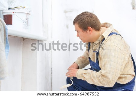 builder looking at the paint wall with roller in hands - stock photo