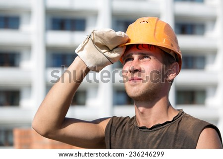 Builder man worker with hard hat looking into distance on construction site background - stock photo