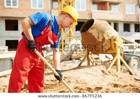 builder man working with shovel during concrete cement solution mortar preparation at construction site - stock photo