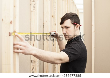 builder measuring space between cls studs doing partitioning - stock photo