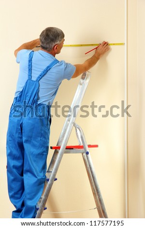 Builder measuring wall in room close-up - stock photo