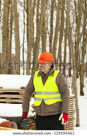 Builder near the building materials in winter - stock photo