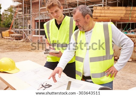 Builder On Building Site Discussing Work With Apprentice - stock photo