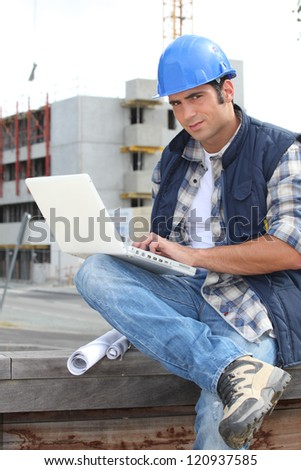 Builder on site with a laptop - stock photo