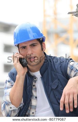 Builder on walkie talkie - stock photo