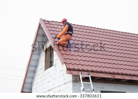 builder performs installation gable roof tiles of metal - stock photo