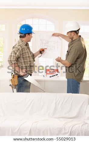 Builder pointing at ground plan, discussing project with architect. - stock photo