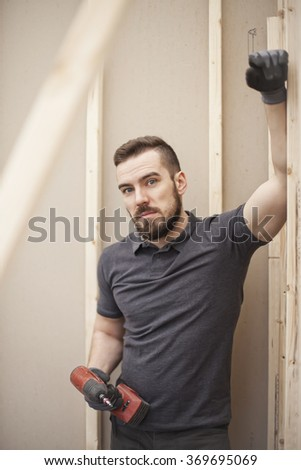 builder posing against plasterboard partition - stock photo