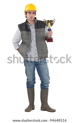 Builder proudly holding trophy