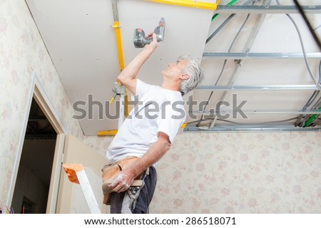 Builder putting up a suspended ceiling - stock photo