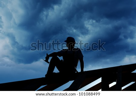 Builder resting on top of roof structure - silhouette against stormy sky - stock photo