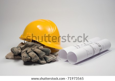 Builder's equipment - blueprints of architecture interior, protective gloves and industrial helmet