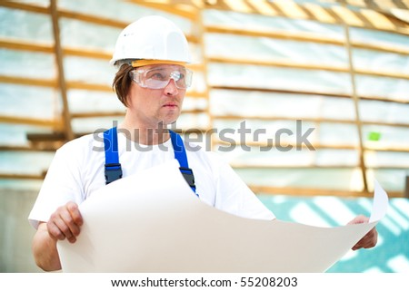 builder seriously looking at the construction project - stock photo