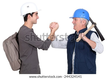 Builder shaking hands with young apprentice - stock photo