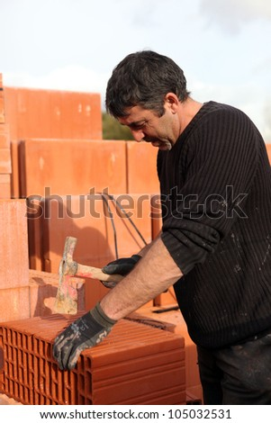Builder shaping a brick - stock photo
