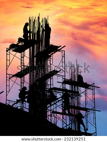 Builder silhouette of construction worker on scaffold  - stock photo