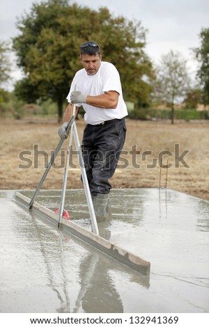 Builder smoothing a concrete foundation - stock photo