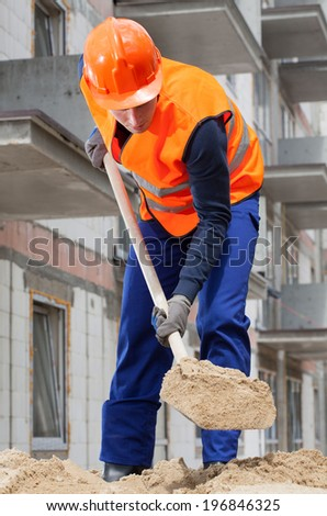 Builder spanning sand with a spade, vertical