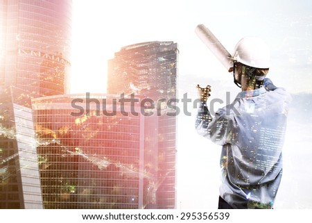 builder standing and pointing at skyscraper - stock photo