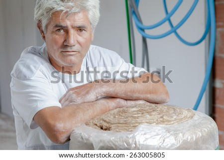 Builder stood with loft insultaion - stock photo