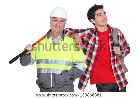 Builder stood with new employee - stock photo