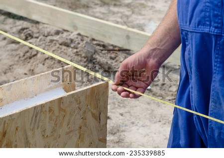 Builder taking a diagonal measurement into a corner of the new build before beginning to install insulated wooden wall panels - stock photo