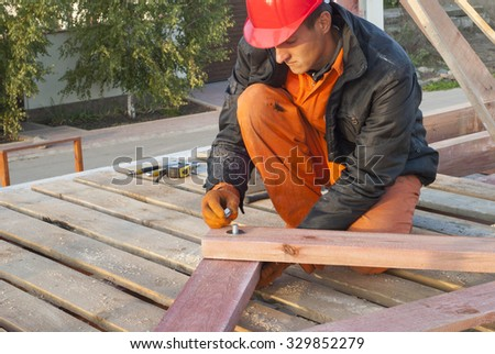 Builder tighten the screws on the connecting pin - stock photo