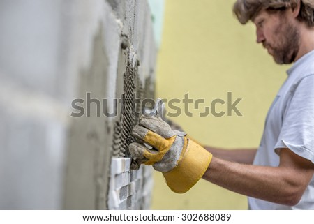 Builder tiling a concrete wall with decorative ornamental tiles lining up a tile with his gloved hands to seat into the tiling cement on the wall, profile view along the length of the wall. - stock photo