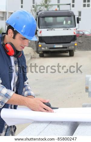 Builder unrolling plan - stock photo