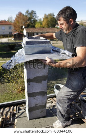 Builder using zinc flashing in the construction of a pillar - stock photo
