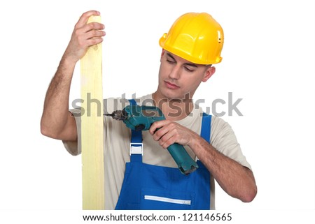 Builder with a cordless drill - stock photo