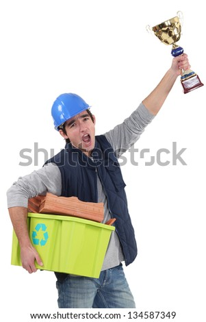 Builder with a trophy recycling material - stock photo