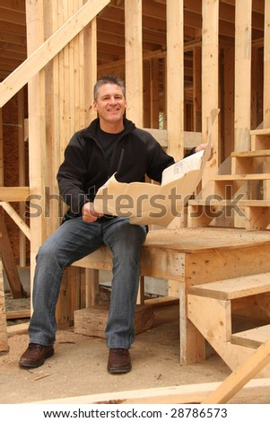 Builder with blue prints in a house under construction. - stock photo