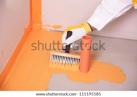 builder with brush applies waterproofing on the floor of the bathroom - stock photo
