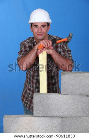 Builder with hammer and timber next to a block wall - stock photo
