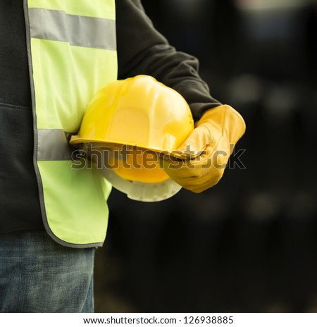 builder with small computer and gloves - stock photo