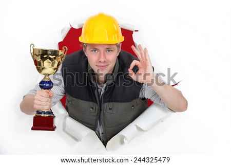 Builder with trophy making OK sign - stock photo