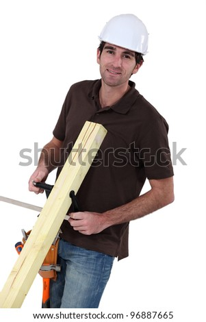 Builder with wood in a vice - stock photo