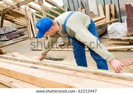 builder worker at roofing works measuring length of wood timber with measuring tape - stock photo