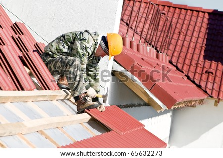 builder worker at roofing works on clay tiling with hammer screw nails - stock photo