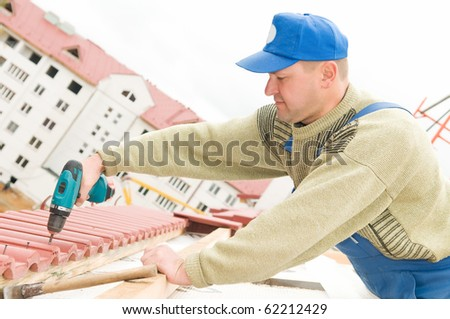 builder worker at roofing works on tiling with screwdriver - stock photo