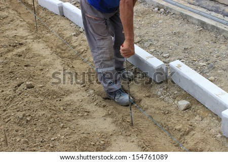 builder worker checking distance with tape measure at construction site. worker measure space for concrete curbs of new sidewalk